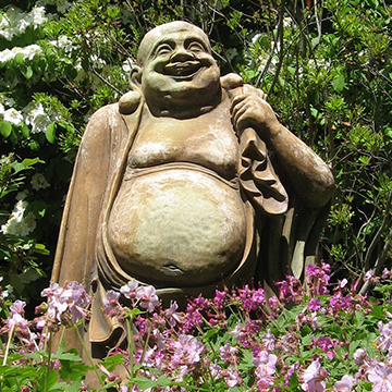Smiling Buddha statue in a landscaped bed