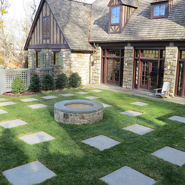 Enclosed yard behind a stone house with placed pavers and a central water feature
