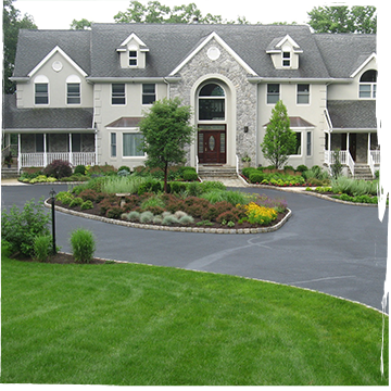 Circle driveway with a landscaped island of a tree and flowering bushes in front of a grey house