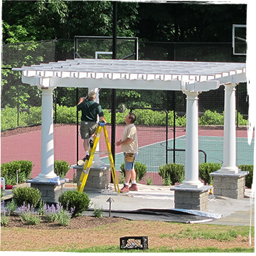 Two men installing a pergola beside a tennis court