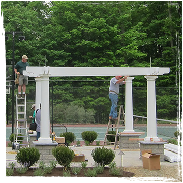 Two men on ladders install beams on a pergola in front of a tennis court