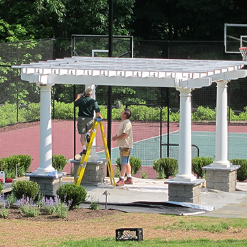 Two men on ladders assembling a white pergola