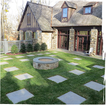 Stone firepit with randomly placed bluestone pavers in a backyard
