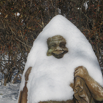Snow piled on top of a smiling Buddha statue
