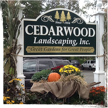 Cedarwood Landscaping business sign with halloween decorations including pumpkins, burlap, and yellow mums
